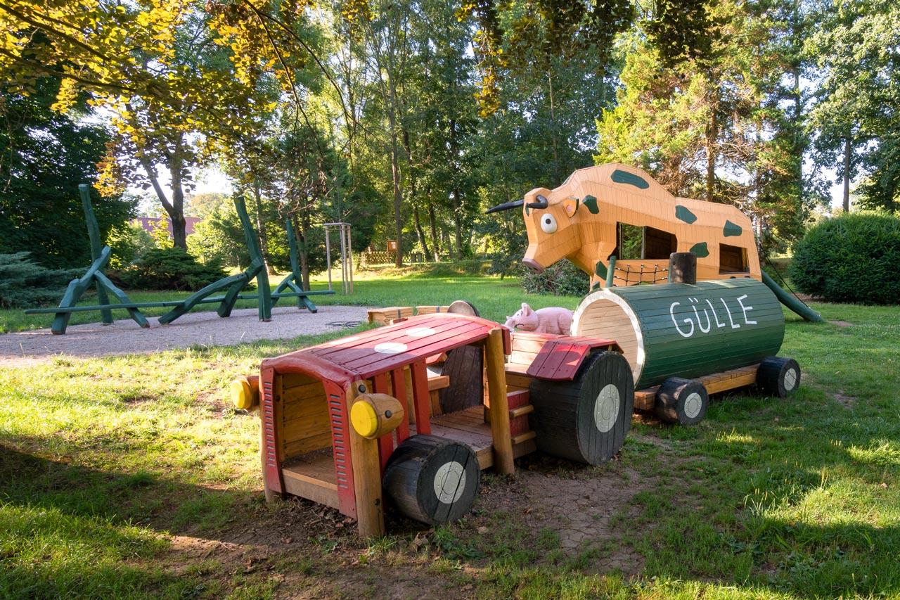 Park Laucha - Spielplatz mit großer Kuh, Heuballen, Traktor, Schwein und Sitzgelegenheiten
